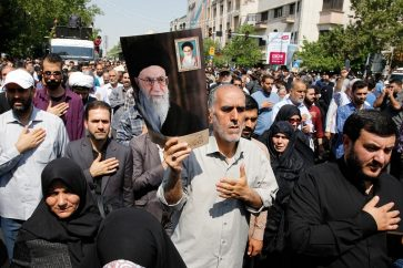 Iranians as hold poster of Iranian supreme leader Ayatollah Ali khamenie mourn during a funeral procession for 150 Iranian soldiers killed in the Iran-Iraq war (1980-1988), whose bodies were recovered from battlefields, in Tehran, Iran, on June, 27, 2019.